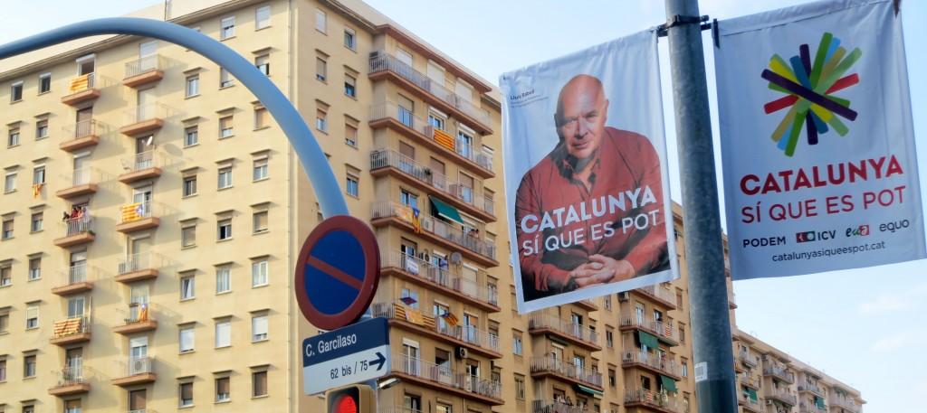 Cartell electoral de Catalunya Sí que Es Pot, amb les estelades al fons.