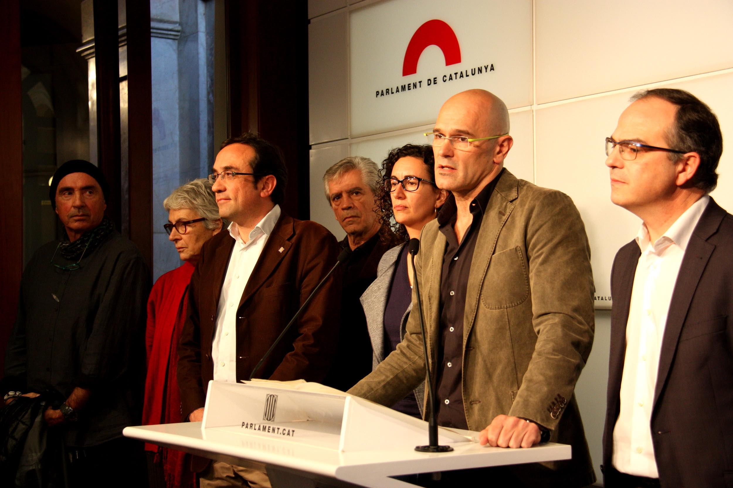 Lluís Llach, Muriel Casals, Josep Rull, Eduardo Reyes, Marta Rovira i Raül Romeva en conferència de premsa per a explicar la proposta d'acord d'investidura amb la CUP el 22 de desembre del 2015